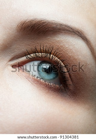 Close-up shot of female eye with bright brown makeup - stock photo