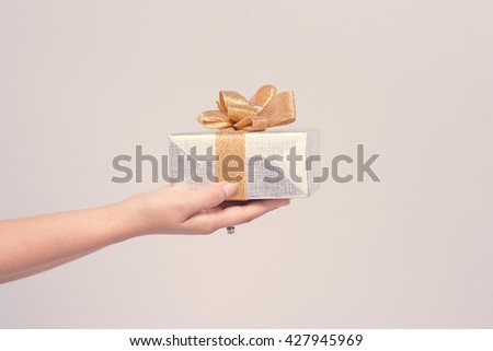 Close up shot of female hands holding a small gift wrapped with pink ribbon. Small gift in the hands of a woman. Shallow depth of field with focus on the little box. - stock photo