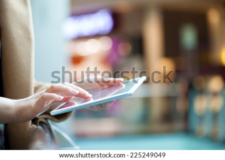Close-up shot of female hands using touchpad in public place. Defocused interior in background - stock photo
