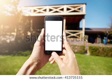 Close up shot of female holding mobile phone with blank copy space screen for your text or information content. Woman using wireless internet connection outdoor, checking e-mail. Selective focus  - stock photo