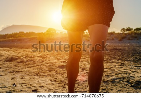 Close up shot of female woman legs running during sunset on the golden sand beach in Greece island.