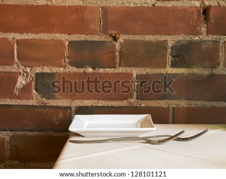 Close-up shot of fork and plate on restaurant table against bricked wall.