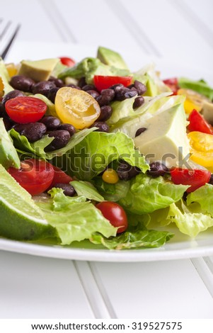 Close up shot of fresh homemade southwest black bean lime salad with corn, cherry tomatoes, lettuce, avocado, and black beans with vinaigrette dressing for clean eating - stock photo