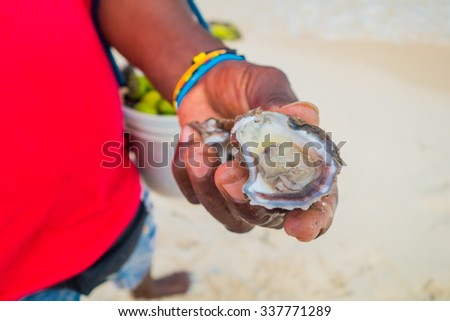 Close up shot of fresh opened clam held by a beach vendor in Playa Blanca, Colombia