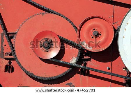 Close-up shot of gears and chains on a old piece of farming equipment. - stock photo