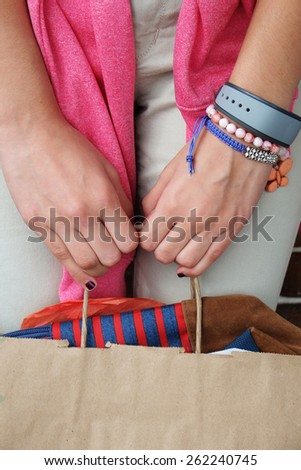 Close up shot of Girl's hands  holding a brown paper shopping bag  - stock photo