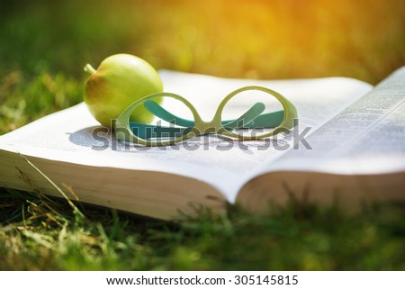 Close-up shot of glasses on a book along with an apple on a green grass - stock photo