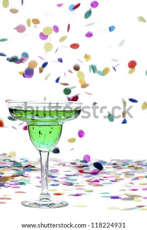 Close-up shot of green alcohol and confetti against white background. - stock photo