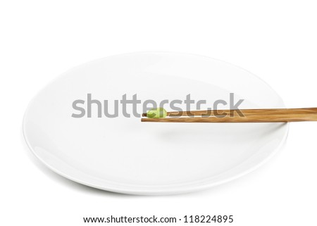 Close-up shot of green bean on chopstick with plate on white surface. - stock photo