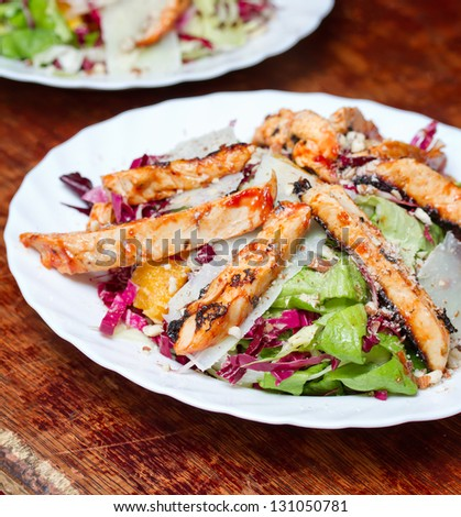 Close-up shot of grilled chicken slices on fresh salad and parmesan cheese - stock photo