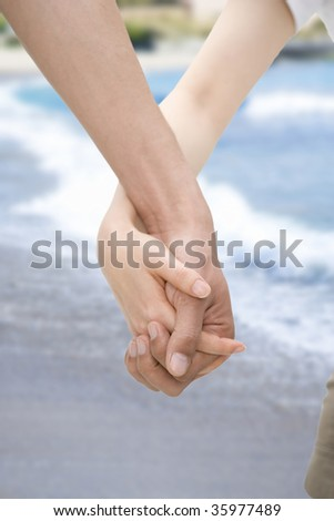Close-up shot of hand in hand with the sea