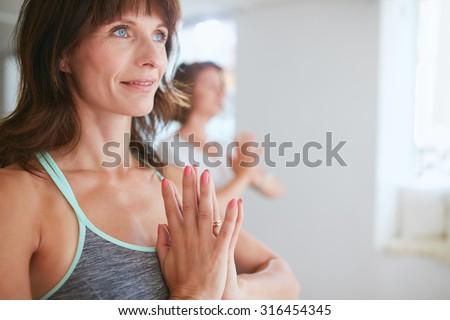 Close up shot of happy mature woman doing yoga looking away smiling. Women in yoga pose vrikshasana using Namaste. - stock photo