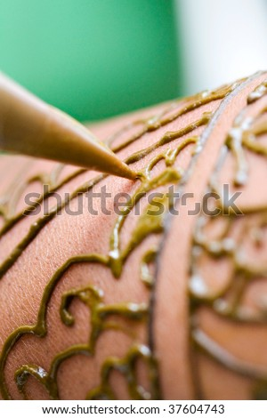 Close Up Shot of Henna being applied to the hands and arms of a hindu bride - stock photo