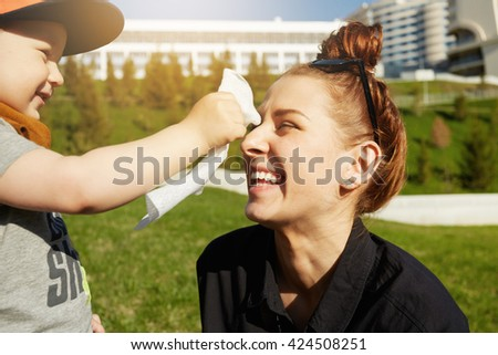 Close up shot of hipster teenage girl spending time with her little nephew on summer morning in the city park. Beautiful young mother with her adorable son in stylish clothes having fun together  - stock photo