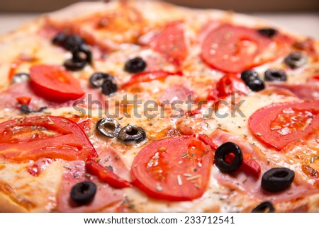 Close-up shot of Italian pizza with ham, tomatoes and olives, selective focus   - stock photo