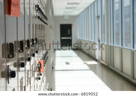 close-up shot of lockers in a row in hallway with exit door in center of shot - stock photo