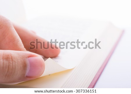 Close-up shot of male fingers turn new page of a book - stock photo
