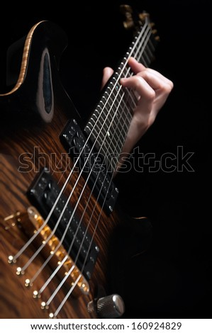 close up shot of male hand playing vintage brown guitar over black - shallow DOF with focus placed on strings - stock photo