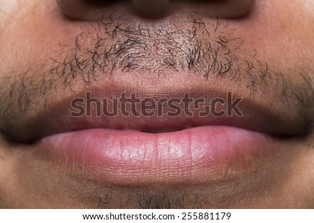 Close up shot of male lips with a mustache and a gentle smile