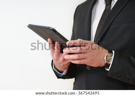close up shot of man's hands holding a tablet in black suit on white background; business concept