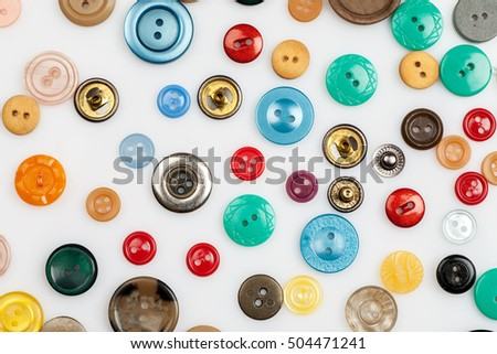 Close-up shot of many different buttons on a white background, flat lay pattern