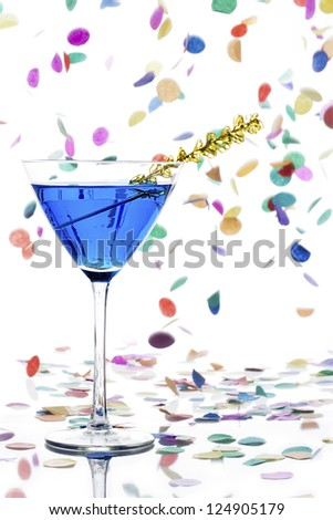 Close-up shot of martini glass with blue curacao and yellow streamers while colorful confetti falling on plain white background. - stock photo