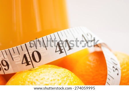 Close up shot of measuring tape in inches, around oranges and glass of juice - stock photo
