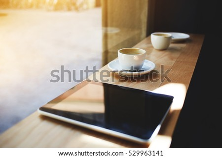 Close up shot of modern touch pad with blank screen lying on table near cup of coffee in cafe interior. Digital tablet as device for internet network connection and multimedia applications