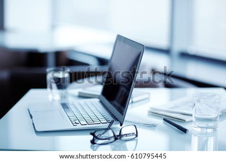 Close-up shot of modern work place: laptop, notebooks and other stationery located on office desk, blurred background
