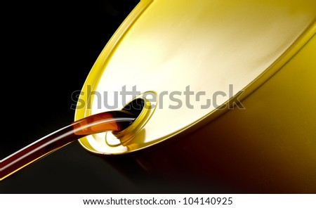Close up shot of oil flowing out of yellow barrel - stock photo