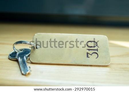 Close up shot of old hotel room key shot on wood front desk - stock photo