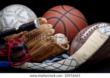 Close up shot of old soccer ball, basketball, baseball, football, bat, hockey stick, baseball glove and cleats - stock photo