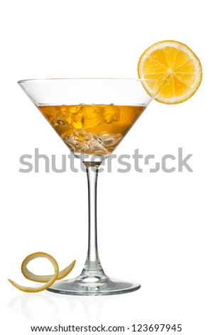 Close-up shot of orange juice with ice cubes in martini glass while peeled orange skin on white surface.