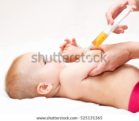 Close-up shot of pediatrician ready to give an intramuscular injection of a vaccine to a baby girl