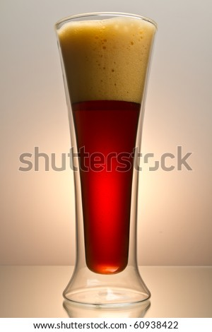 Close up shot of pint of dark beer shot on rich brown background with space for copy - stock photo