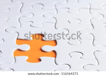 close up shot of plain puzzle with a missing piece - stock photo