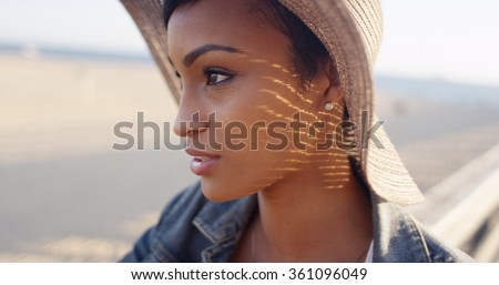 Close up shot of pretty black woman at the beach wearing sunhat - stock photo