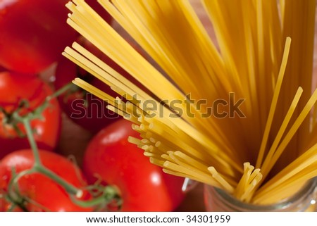 Close up shot of raw spaghetti with some tomatoes on the background - stock photo