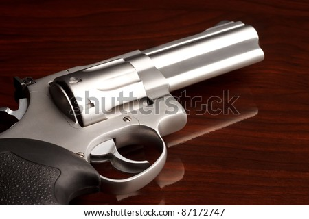 Close-up shot of .357 revolver on reflective wooden surface - stock photo