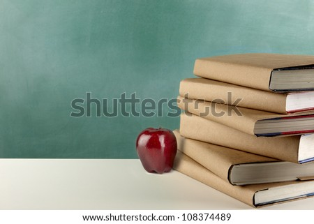 close-up shot of school books, red apple and blackboard with space for copy - stock photo