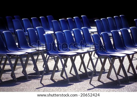 close up shot of several blue chairs in a row