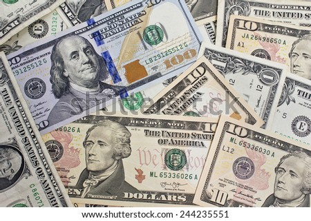 Close Up shot of several dollar bills laying chaotically around.One,ten and hundred dollar bills have been used. - stock photo