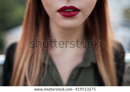 close up shot of sexy red female lips; macro shot of purple lipstick on lips of young attractive woman; - stock photo