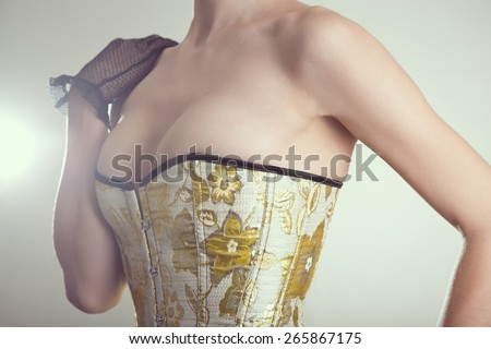 Close-up shot of sexy young woman in corset with golden embroidery, studio shot with vintage tone  - stock photo