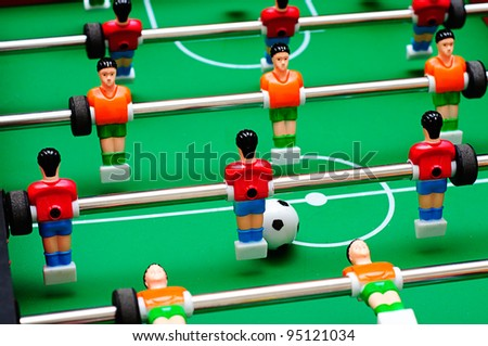 close up shot of soccer table game with green field and red and yellow plastic football players - stock photo