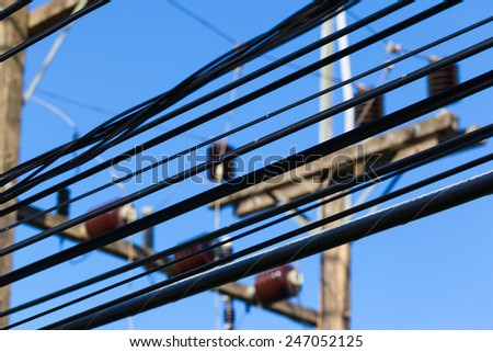 close up shot of some high voltage electricity cables over the blue sky - stock photo
