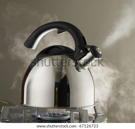 Close up shot of steaming tea kettle. Heater glow under the kettle. - stock photo