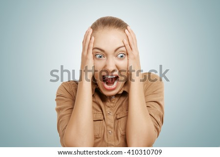 Close up shot of stressed and shocked young blonde businesswoman screaming with desperate and horrified expression, mouth wide open. Negative human face expressions, emotions, body language reaction - stock photo