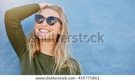 Close up shot of stylish young woman in sunglasses smiling against blue background. Beautiful female model with copy space. - stock photo