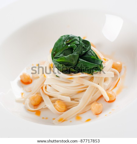 Close up shot of tagliatelle pasta with spinach and chick peas. - stock photo